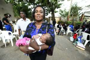 Edo State Attorney General and Commissioner for Justice Professor Yinka Omorogbe carries the one-month-old child of a migrant brought home to Nigeria from Libya.