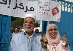 Ennahdha's presidential candidate Abdelfattah Mourou and his wife show their ink-stained fingers after casting their votes on the outskirts of the capital Tunis.  By Fethi Belaid (AFP)