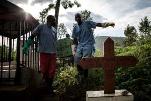Epidemic: Health workers in the eastern city of Butembo carry a coffin containing a victim of Ebola.  By JOHN WESSELS (AFP)