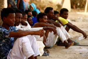 Eritrean migrants sit at the Wadi Sherifay camp on May 2, 2017, after being caught by Sudanese border security illegally crossing the Eritrea-Sudan border in the eastern Kassala state