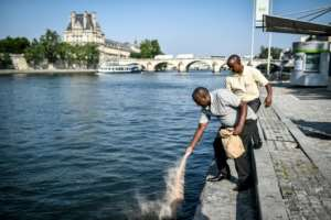 Eric and Bernard pour soil from Bisesero land into the Seine river in Paris.  By STEPHANE DE SAKUTIN (AFP)