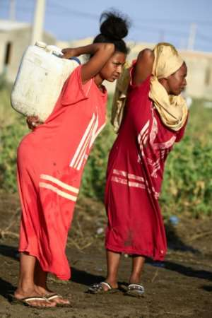 Ethiopian women who fled fighting in Tigray carry water containers at the 'Village 8' facility in Sudan's eastern Gedaref state.  By ASHRAF SHAZLY (AFP)