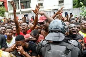 Fans cried and chanted outside the hospital where Ivorian singer DJ Arafat died after a traffic accident.  By ISSOUF SANOGO (AFP)