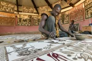 Fakaha villagers plunge knives or sticks into bowls of colour to transform the white cotton into a work of art covered with animal motifs and figures in masks. By SIA KAMBOU (AFP)