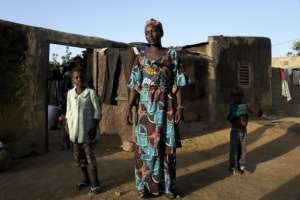 Fatoumara Dja poses with her children in front of the house in Segou, where they found shelter after fleeing their village.  By MICHELE CATTANI (AFP)