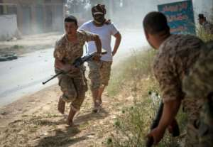 Fighters loyal to Libya's internationally recognised unity government run for cover during recent clashes with the self-styled Libyan National Army. By FADEL SENNA (AFP/File)