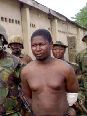 File picture showing Boko Haram founder Mohammed Yusuf, 39, surrounded by soldiers at a barracks after his capture in 2009