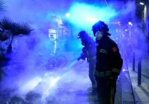Firefighters put out a fire after a demonstration against a curfew in Barcelona as virus cases spike around Europe.  By Josep LAGO (AFP)