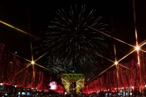 Fireworks erupt over the Arc de Triomphe during the New Year's celebrations on Champs Elysees avenue, where tens of thousands gathered despite a grueling transport strike.  By Martin BUREAU (AFP)