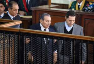 Former Egyptian president Hosni Mubarak (C), who was ousted during a popular uprising in 2011, is escorted by his two sons Alaa (R) and Gamal (L) for a session in the retrial of members of the now-banned Muslim Brotherhood.  By MOHAMED EL-SHAHED (AFP/File)