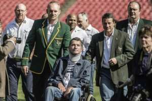 Former South African Rugby World Cup winner Joost van der Westhuizen (front) is assisted by former captain Francois Pienaar (2L) during a re-enactement of the 1995 Rugby World cup victory team photo at Ellis Park in Johannesburg on June 24, 2015