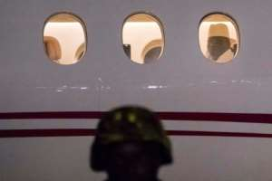 Former president Yaya Jammeh, who led Gambia for 22 years, looks through the plane window as he leaves the country on January 21, 2017 from Banjul airport
