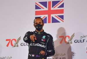 Formula One world champion Lewis Hamilton -- seen here celebrating his victory in Bahrain -- has tested positive for the virus.  By Giuseppe CACACE (POOL/AFP)