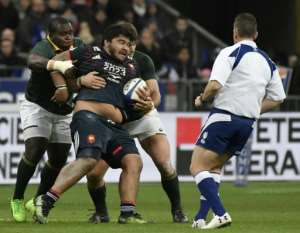 France's prop Sébastien Taofifenua (C) is tackled during their match against South Africa's Springboks in Saint-Denis, on the outskirts of Paris, on November 18, 2017