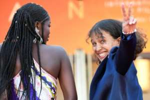 French actress and film director Mati Diop (R) flashes the victory sign as she arrives with Senegalese actress Mama Sane for the screening of the film