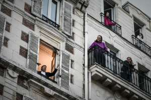 French opera tenor singer Stephane Senechal performs 'O Sole Mio' from his window in Paris on the tenth day of a strict lockdown in France.  By PHILIPPE LOPEZ (AFP)
