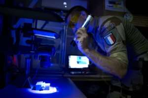 French troops use a ultraviolet light and other tools to investigate fingerprints and other clues on bomb making materials.  By MICHELE CATTANI (AFP)