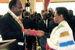 Gabon's Constitutional Court President Marie Madeleine Mborantsuo hands the Gabonese constitution to Ali Bongo Ondimba, after he was sworn in as president in 2009