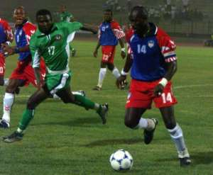 George Weah, right, wears the number 14 jersey as he plays for the Liberian national football team in 2002