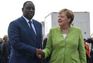 Germany's Chancellor Angela Merkel met by Senegal's President Macky Sall upon her arrival at Diass Airport on the outskirts of Dakar.  By SEYLLOU (AFP)