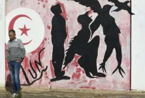 Graffiti depicts a man metamorphosing into a bird symbolising freedom, in Mohamed Bouazizi Square -- named after the street vendor who sparked the revolution -- in the town of Sidi Bouzid.  By Fethi Belaid (AFP/File)