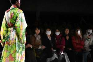 Guests wear masks as a model presents a creation by Dries Van Noten during the Women's Fall-Winter 2020-2021 Ready-to-Wear collection fashion show in Paris.  By Anne-Christine POUJOULAT (AFP)