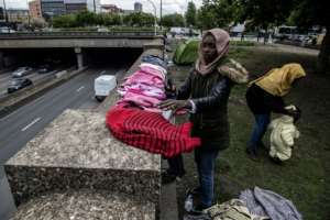 Hana, a Sudanese refugee living in Paris with her two children, aged 2 and 4, arranges clothing on a wall overlooking the Paris ring road. By Christophe ARCHAMBAULT (AFP)