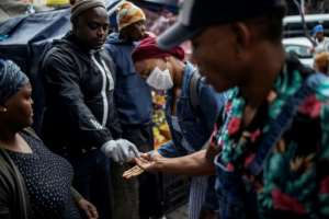 Hand hygiene: Passenger get a cleansing dollop at the Wanderers taxi rank in central Johannesburg.  By Michele Spatari (AFP)