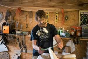 Hand-made: Patrick Burnett sands a wooden surfboard in his workshop, near Cape Point.  By RODGER BOSCH (AFP)