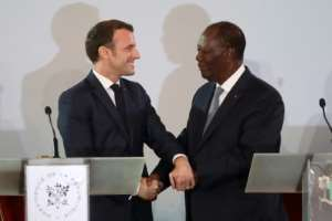 Handshake: Macron and Ouattara at their press conference in Abidjan last Saturday.  By Ludovic MARIN (AFP)