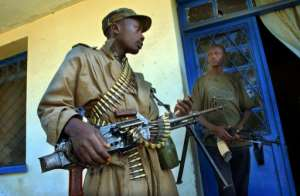 Heavily armed militiamen guard a party office in Bunia, the main city in the volatile Ituri province.  By MARCO LONGARI (AFP/File)