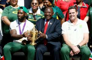 South African President Cyril Ramaphosa holds the Rugby World Cup trophy with Springboks captain Siya Kolisi.  By Phill Magakoe (AFP)