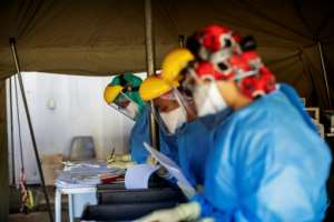 Health workers fill out documents before performing tests for COVID-19 coronavirus on other health workers at the screening and testing tents set up at the Charlotte Maxeke Hospital in Johannesburg.  By Michele Spatari (AFP)