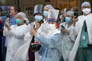 Health workers react to people applauding in front of Mount Sinai Hospital in Queens, New York to show gratitude to medical staff and essential workers on the front lines of the coronavirus pandemic.  By Johannes EISELE (AFP)