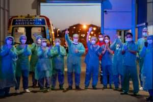Healthcare workers dealing with the new coronavirus crisis applaud in return as they are cheered on by people outside a hospital in Burgos, Spain.  By CESAR MANSO (AFP)