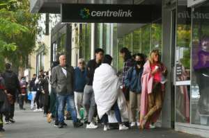 Hundreds of people queue outside a government welfare centre, Centrelink, in Melbourne on March 23, 2020, as jobless Australians flood unemployment offices.  By William WEST (AFP/File)