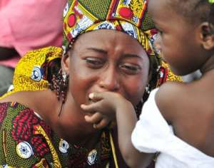 A young girl tries to comfort her mother during a burial ceremony.  By Sia Kambou (AFP/File)