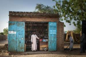 Ibrahim Hassan, a 42-year-old Sudanese trader and refugee in Treguine, poses in front of his shop in the adjoining town of Hadjer Hadid. By Amaury HAUCHARD (AFP)