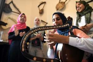 Iman Haddo (C), a 20-year-old musician, says she instantly fell in love with the semsemia when she was a teenager after attending a local concert with her father..  By Khaled DESOUKI (AFP)