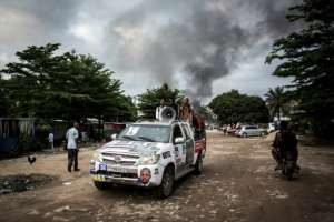 In the early hours of Thursday, arsonists hit a large electoral commission warehouse in central Kinshasa, setting it ablaze and damaging election materials.  By John WESSELS (AFP)