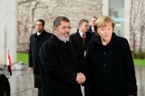 In this file photo taken in January 2013 German Chancellor Angela Merkel shakes hands with Egypt's then president Mohamed Morsi in Berlin.  By John MACDOUGALL (AFP/File)