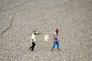 In this photo taken on June 20, 2019, Indian worker carry the last bit of water from a small pond in the dried-out Puzhal reservoir on the outskirts of Chennai.  By ARUN SANKAR (AFP/File)