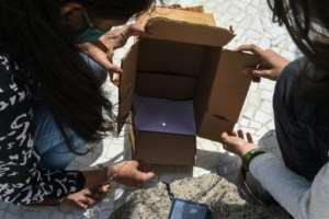 In India's Gujarat, members of a state science council watched the eclipse safely using a pinhole box.  By SAM PANTHAKY (AFP)