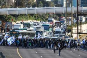 Israelis of Ethiopian origin block Tel Aviv highway as they protest against police violence and racism after an officer shot a young community member dead.  By JACK GUEZ (AFP)