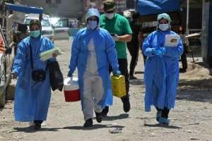 Iraqi medics arrive in Sadr City to test residents for COVID-19.  By AHMAD AL-RUBAYE (AFP)
