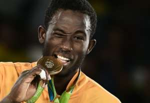 Ivory Coast's Cheick Sallah Junior Cisse poses with his gold medal on the podium after the men's taekwondo event in the -80kg category as part of the Rio 2016 Olympic Games, on August 19, 2016