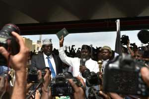 Kenya's opposition leader Raila Odinga holds up a bible as he swears himself in as the 'people's president' before thousands of supporters at a January 30 mock ceremony in Nairobi.  By TONY KARUMBA (AFP/File)
