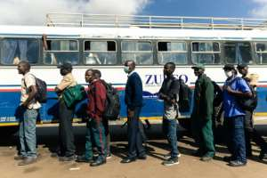 Key workers exempted from the lockdown prepare to board a government-subsidised bus in Harare.  By Jekesai NJIKIZANA (AFP)