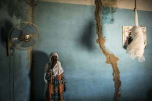 Khady, who lives on the outskirts of the forest, stands next to cracks in her walls caused by explosions from the quarry.  By JOHN WESSELS (AFP)