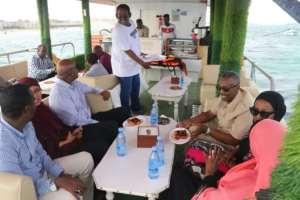 La Lanterna owner Abdulkadir Mohamed Ibrahim serves customers on board his floating restaurant.  By Abdirazak Hussein FARAH (AFP)